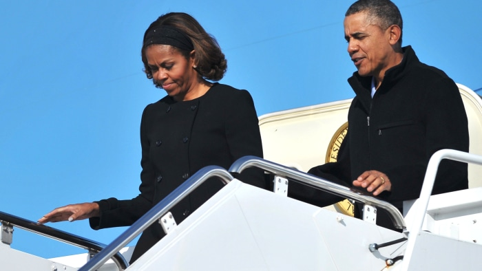 US President Barack Obama and First Lady Michelle Obama step off Air Force One upon arrival at Andrews Air Force Base in Maryland on March 9, 2014. Ob...