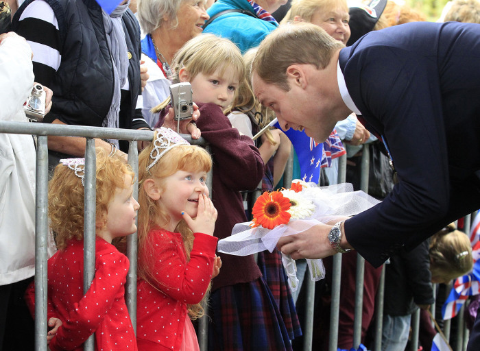 TOPSHOTS  Britain's Prince William (R) receives flowers from three-year-old twins Lola and Milly Barnett  during a walkabout in Seymour Square during ...