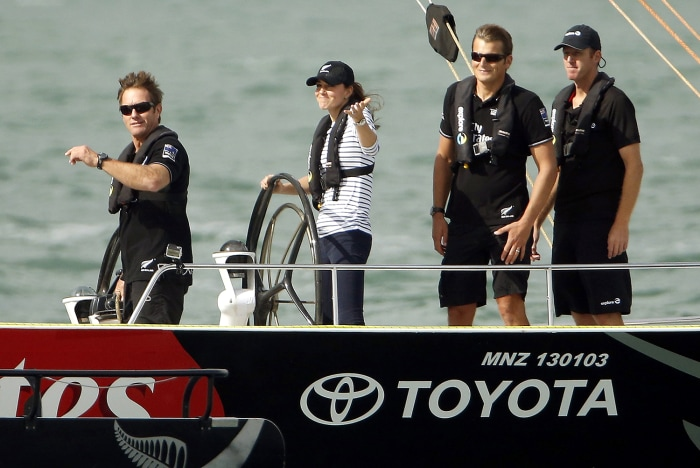 Catherine (2nd L), the Duchess of Cambridge, gestures as she steers an America's Cup yacht towards her husband, Britain's Prince William, after she cr...
