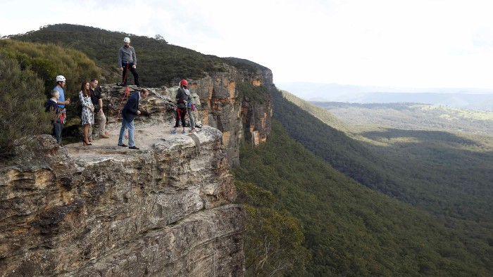 Britain's Prince William (C) looks over the edge of a cliff as he and his wife Catherine, the Duchess of Cambridge, visit the Narrow Neck Lookout and ...