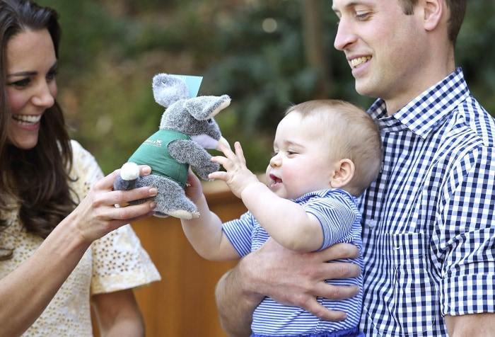 Prince William holds Prince George as Catherine, Duchess of Cambridge, gives him a toy during a visit to the Bilby Enclosure at Sydney's Taronga Zoo A...