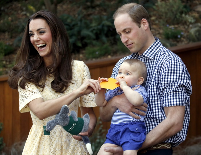 Britain's Kate, the Duchess of Cambridge, and her husband Prince William react as their son Prince George bites a small present that was given to him ...