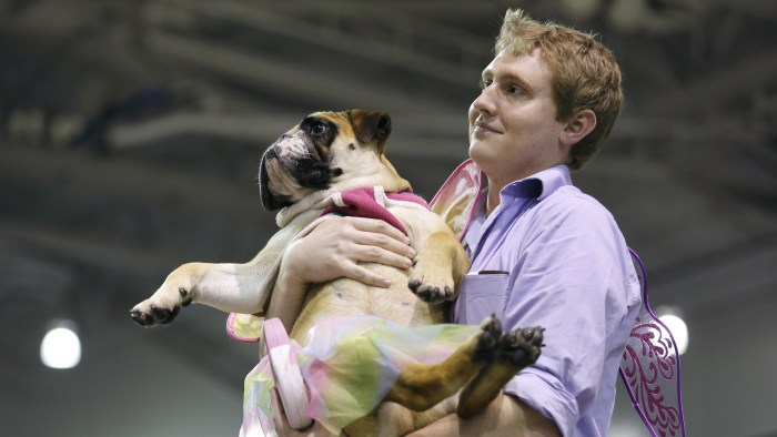 John Jacobson, of Pleasant Hill, Iowa, carries his dog Baby to the stage after it was named the miss congeniality winner at the 35th annual Drake Rela...