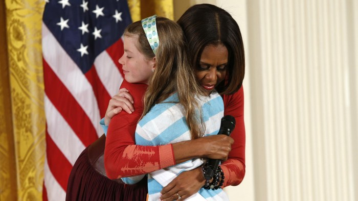 First Lady Michelle Obama hugs Charlotte Bell, 10, who gave the first lady her father's resume and said he had been out of work for three years, as Mi...