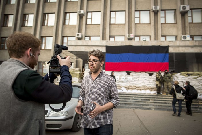 This picture taken on April 21, 2014 shows US journalist Simon Ostrowsky (C) working in front of the City Hall of Slavyansk. The US State Department s...