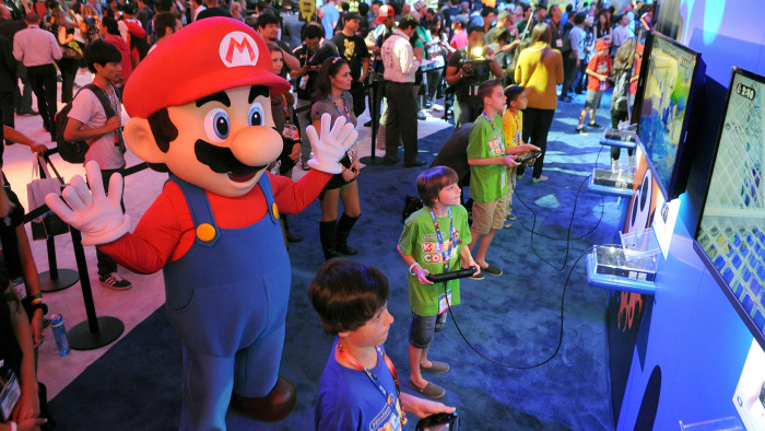 Children try out a new video game at Nintendo's booth during E3 on June 11, 2014, in Los Angeles.