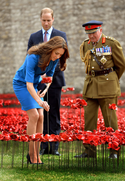 LONDON, UNITED KINGDOM - AUGUST 05:  Catherine, The Duchess of Cambridge adds a ceramic poppy watched by Prince William, Duke of Cambridge and Lord Da...