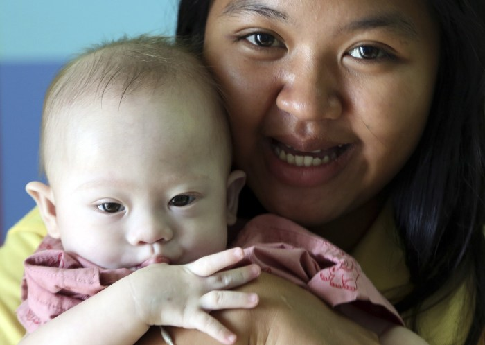 In this photo taken Aug. 3, 2014, Thai surrogate mother Pattaramon Chanbua, a 21-year-old food vendor, poses with Gammy, a nine-month old baby boy who...