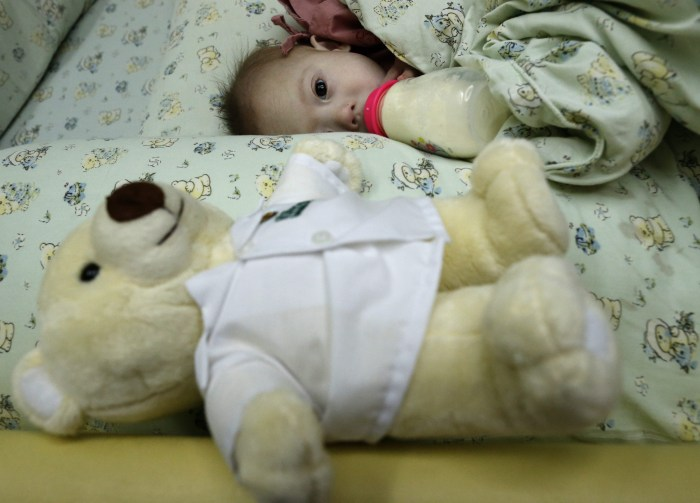 epa04340368 A Thai seven-month-old Down's Syndrome surrogate baby, Gammy or Naruebet Mincharoen drinks from a bottle of milk next to his Teddy bear at...