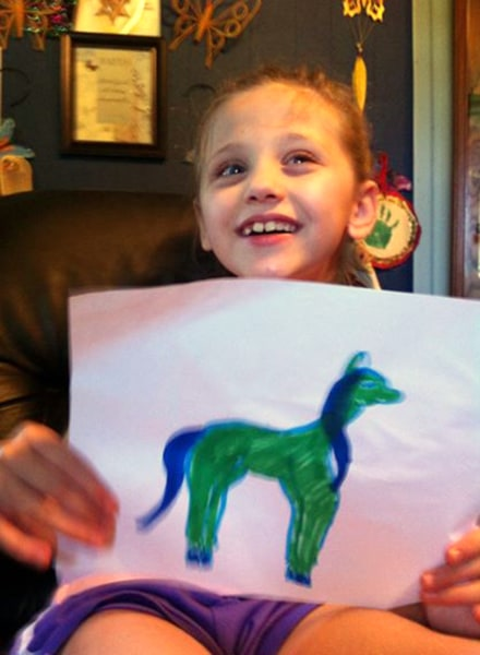 Lex with a homemade horse drawing; she has loved horses since she was 3 years old.