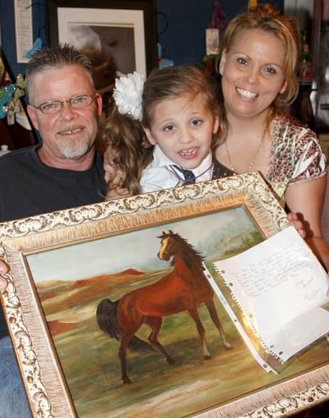 Alexus with her parents and one of the horse pictures she's received; she has no idea she's about to get a horse of her very own.