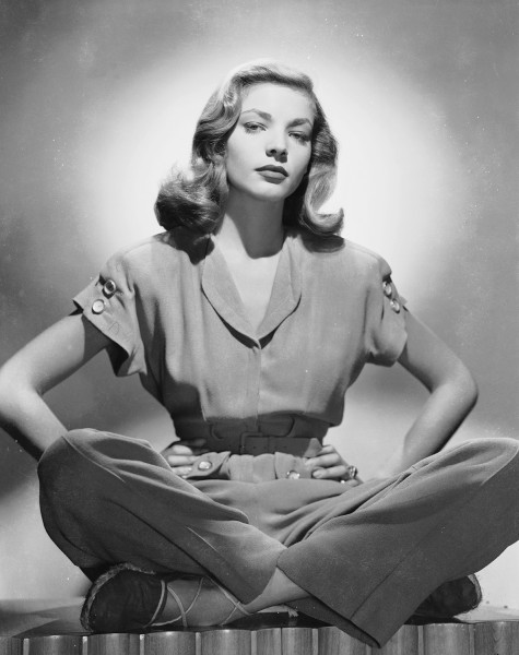 circa 1945:  American screen star Lauren Bacall sitting cross-legged in a trouser suit, with her hands on her hips.  (Photo via John Kobal Foundation/...