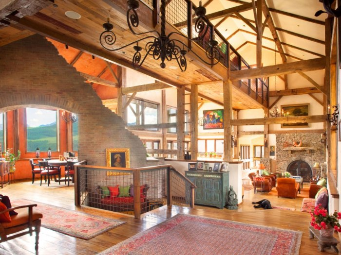 The home's design includes brick fireplaces, beamed ceilings and log-cabin walls.