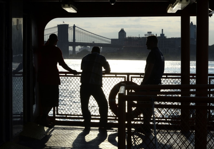 With the Brooklyn Bridge in the background, passengers on the Staten Island Ferry watch the morning sunrise on July 11, 2014, in New York Harbor.