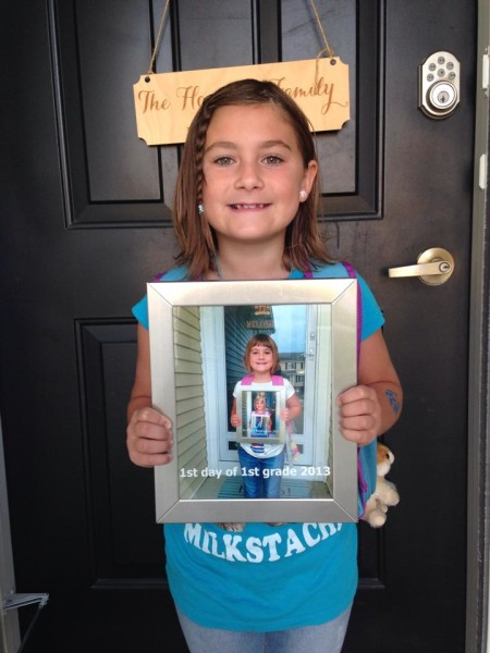 Starting 2nd grade by holding a pic of what she looked like starting 1st grade.
