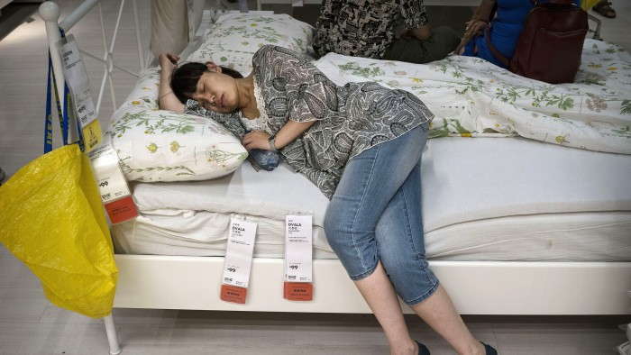 BEIJING, CHINA - JULY 06:  A Chinese shopper sleeps on a bed in the showroom of the IKEA store on July 6, 2014 in Beijing, China. Of the world's ten b...