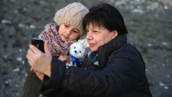 SOCHI, RUSSIA - FEBRUARY 02:  A family takes pictures with Olympic mascot at the beach of Sochi sea port on February 2, 2014 in Sochi, Russia.  (Photo...