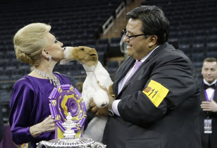 Judge Betty Regina Leininger, left, and handler Gabriel Rangel, pose with Sky, a wire fox terrier, after winning best in show at the Westminster Kenne...