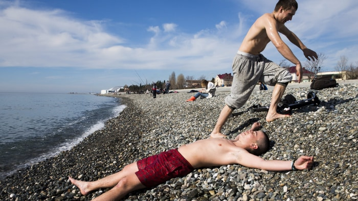 People enjoy the sunny weather at the Black Sea beach with the Fisht Stadium (rear) in the Olympic Park visible in the background, Sochi, ...