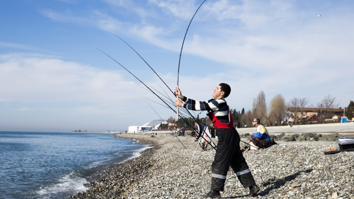 Men cast their fishing rods at the Black Sea beach with the Fisht Stadium (rear) in the Olympic Park visible in the background, Sochi, Rus...