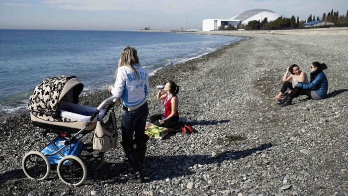 Local residents enjoy nice weather on the beach at the Black Sea near the Olympic Park during the 2014 Sochi Winter Olympics, February 12, 2014. REUTE...