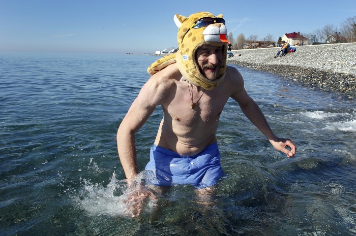 epa04074193 A Russian man swims in the Black Sea outside the Olympic Park at the Sochi 2014 Olympic Games, Sochi, Russia,13 February 2014. Warm weathe...