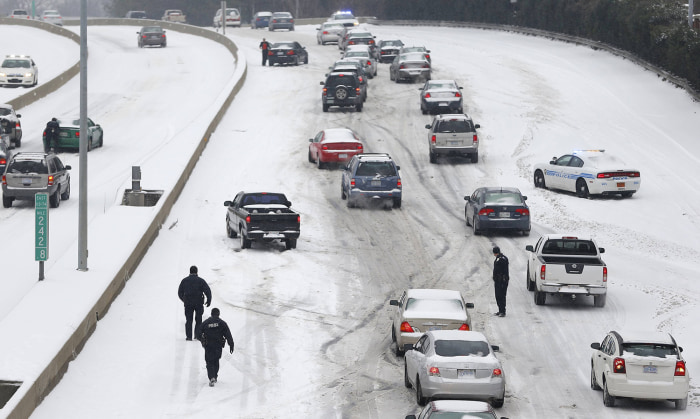 Charlotte Mecklenburg Police Officers work to assist motorists as they attempt to drive up a hill that is covered in snow in Charlotte, North Carolina...