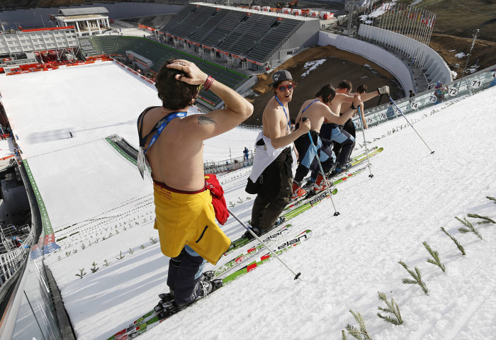 Feb. 10, 2014 - Sochi, Russia - Course workers take off their shirts to enjoy the warm weather as they prepare the landing hill before the Men's Nordi...
