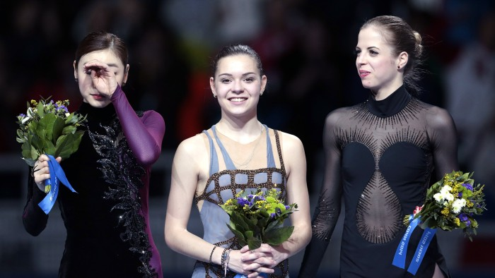 Adelina Sotnikova of Russia, centre, Yuna Kim of South Korea, left, and Carolina Kostner of Italy stand on the podium during the flower ceremony for t...