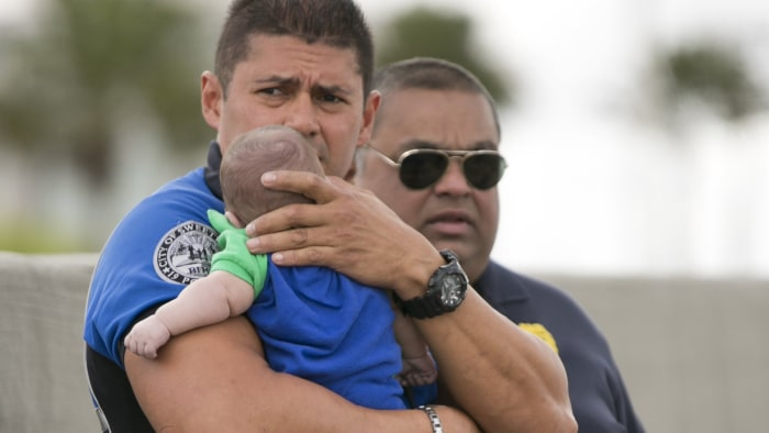 Sweetwater officer Amauris Bastidas keeps a watchful eye waiting for paramedics after aiding a five-month-old Sebastian de la Cruz who stopped breathi...