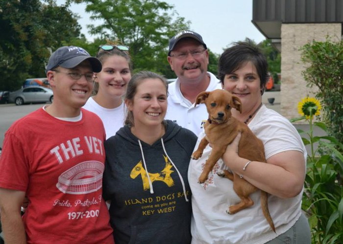 Frank the dog with his foster family and his adoptive family. He was taken home on Aug. 16, 2013.