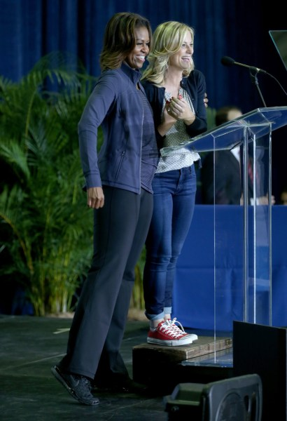 First Lady Michelle Obama stands on stage with actress  Amy Poehler, during a visit to the Gwen Cherry Park NFL/YET Center on February 25, 2014 in Mia...