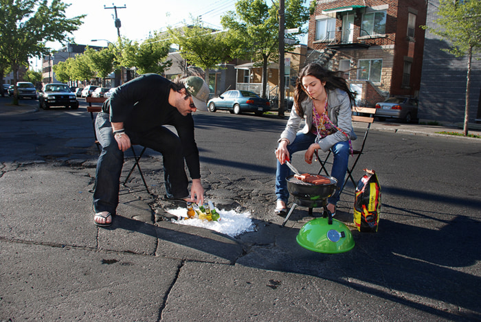 Image: Two people BBQ over a pothole filled with ice cold beer