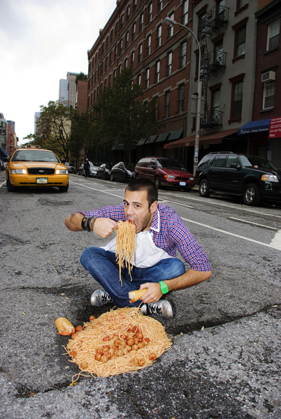 Image: A man sits down for a pasta feast on the streets of New York