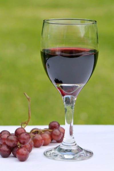Close up of a glass of red wine on a white tablecloth in the garden