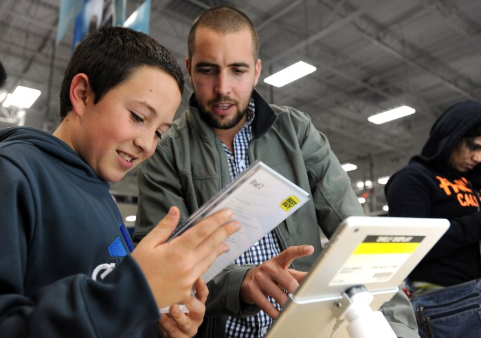 Sabastian Valenzuela, left, and his older brother Alberto compare prices for iPad tablets at a Best Buy on Thanksgiving evening. Best Buy got a shout out from Deal News for making Black Friday deals available a few days before Thanksgiving and matching some of the hottest offers from other retailers.