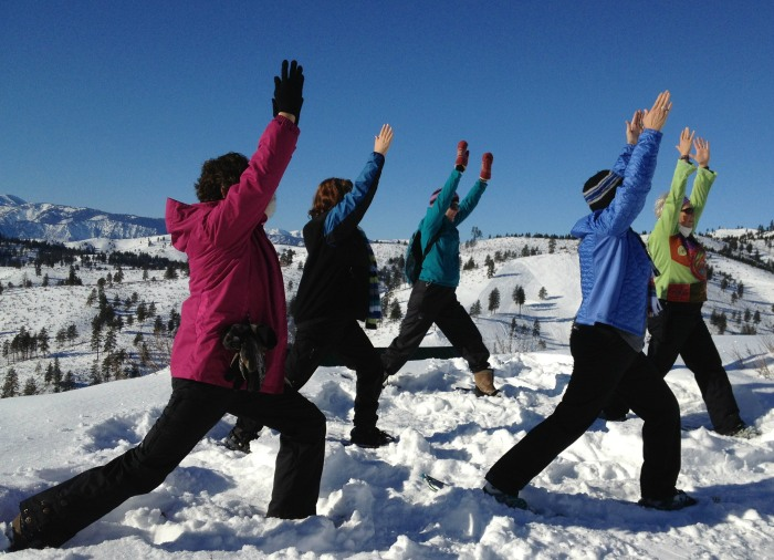 "Snowshoers practice a ""warrior"" pose during a snowga session in Chelan, Wash."