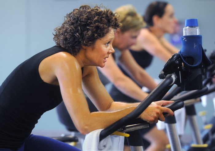 Fitness instructor Sarah Cunnagin of Owensboro, left, watches Larry Simpson during spin class Thursday Nov. 14, 2013,  at the HealthPark. Cunnagin has...