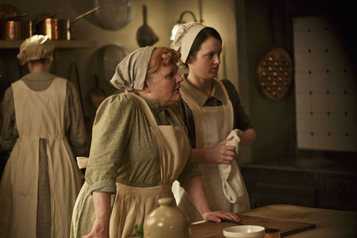 This photo released by PBS and Carnival Film and Television Limited shows, from left, Lesley Nicol as Mrs. Patmore, and Sophie McShera as Daisy, in a ...