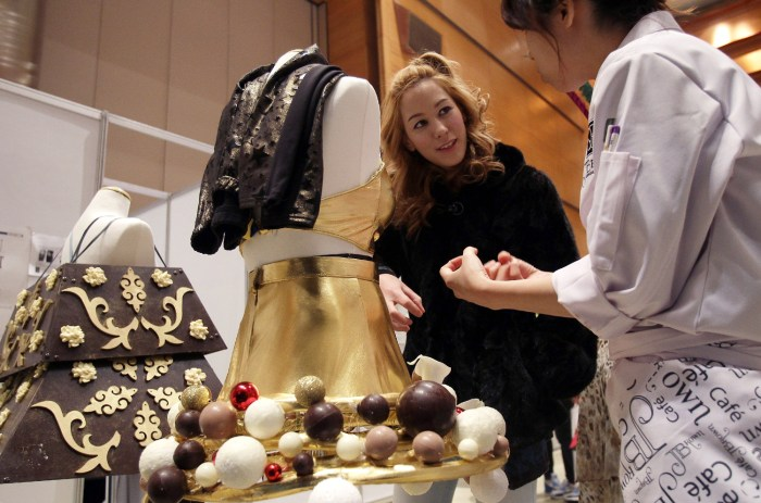 An attendee of the Chocolate Fashion Show gets a closer look at the chocolate dresses.