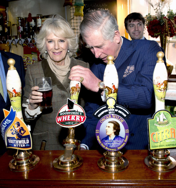 Prince Charles pulls a pint of draught beer as Camilla, The Duchess of Cornwall looks on during a visit to The Bell pub in Purleigh on Jan. 29.