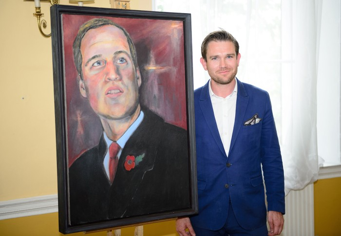 British artist Dan Llywelyn Hall poses for a photograph following the unveiling of the new portrait of the Duke of Cambridge, at the Welsh Office in c...