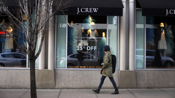 In this March 24, 2014 photo, a pedestrian passes a J.Crew store in the Shadyside shopping district of Pittsburgh. The Commerce Department reports on ...