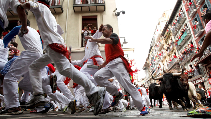PAMPLONA, SPAIN - JULY 10:  Revellers run with Garcigrande's fighting bulls along the Curva de Estafeta during the fifth day of the San Fermin Running...