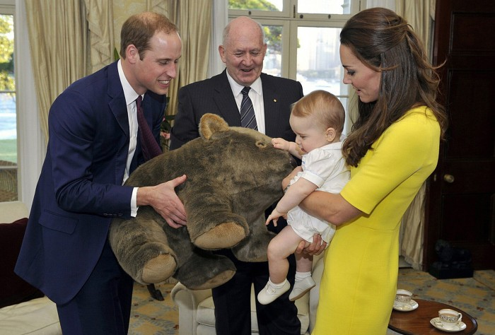 Catherine, the Duchess of Cambridge, holds her son Prince George as his father, Britain's Prince William (L), holds a toy wombat that was given as a p...