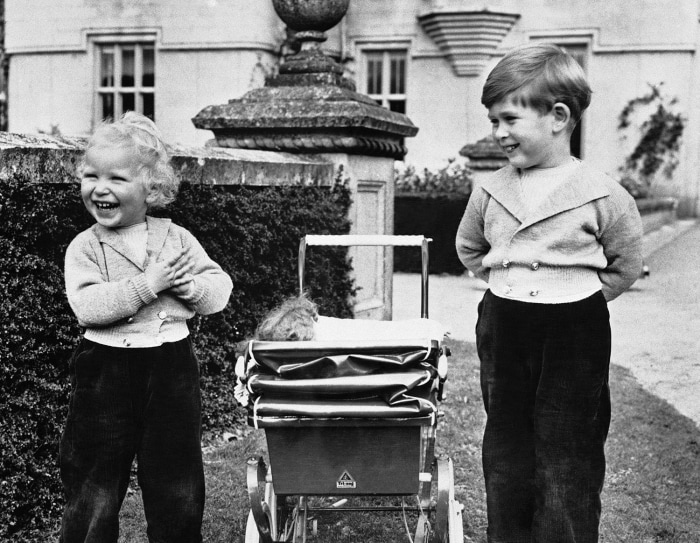 They have a case of the giggles! Prince Charles and his sister, Princess Anne, playing on grounds of Balmoral Castle, Scotland in 1952. They stand on ...