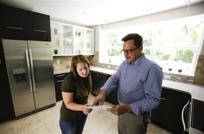 Realtor Greg Gammonley, right, with ConnectRealty.com, shows off a home to prospective buyer Maddie Coker in Orlando, Fla., in this Friday, May 23, 2014 photo.