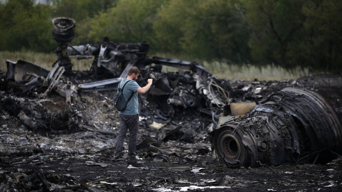 A journalist takes photographs at the site of Thursday's Malaysia Airlines Boeing 777 plane crash near the settlement of Grabovo, in the Donetsk regio...
