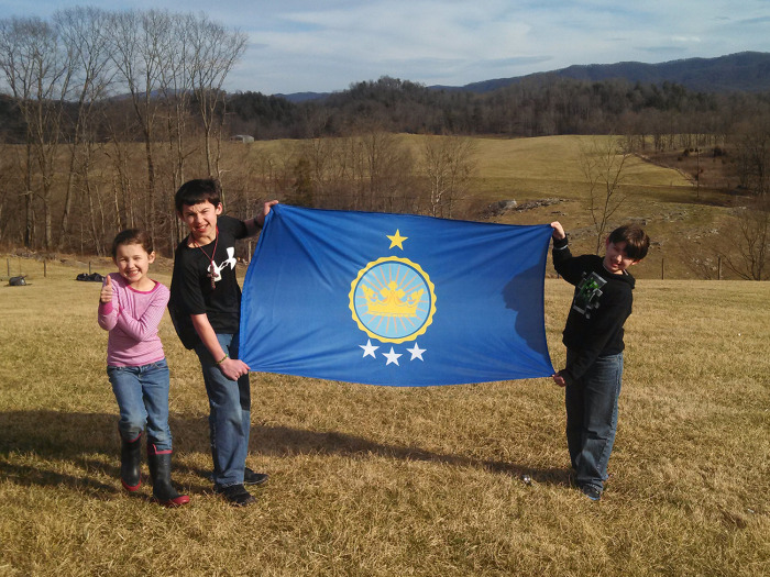 Emily, Justin and Caleb Heaton show off their family flag.