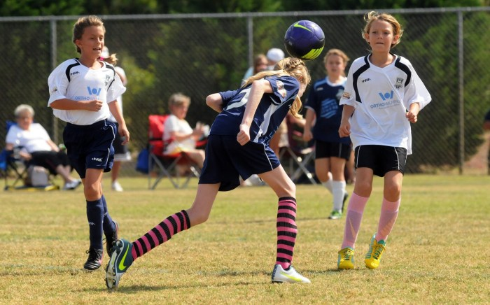 Travel for youth sports is replacing vacations for some families. In this photo from May 10, 2014, Lumina Fitness's Kaitlyn Harrison heads the ball in front of Orthowimington's Elena Berg during a soccer game in Wilmington, N.C.